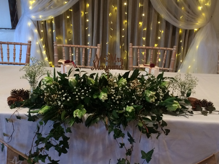 Flowers at the top table of Fitzleroi Barn